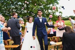 sortie des mariés sous les pompons colorés