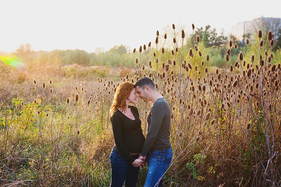 un couple de futurs parents dans un champ et la lumière du soleil couchant