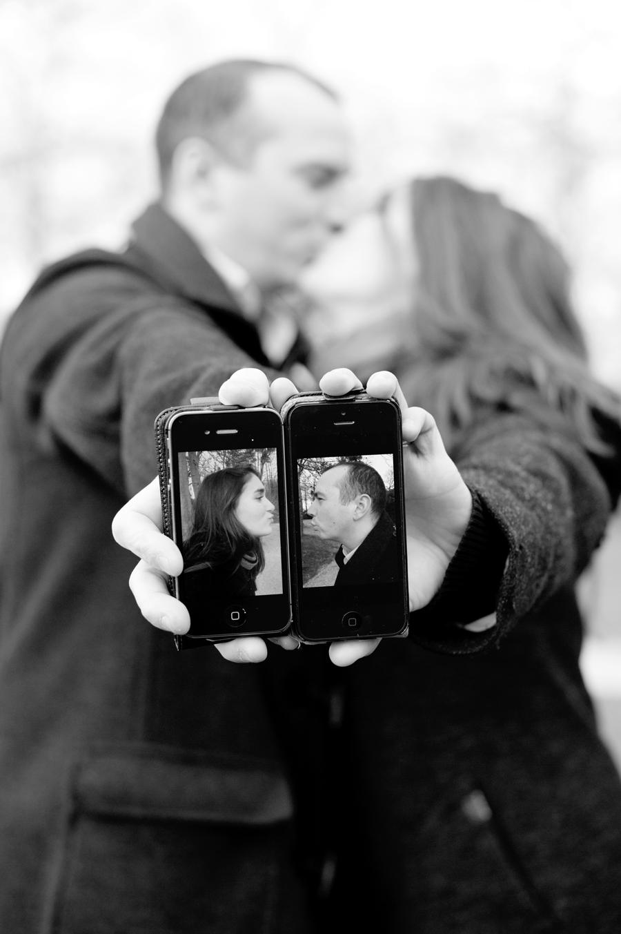 couple s'embrasse et brandit leurs portraits sur téléphone portable au premier plan