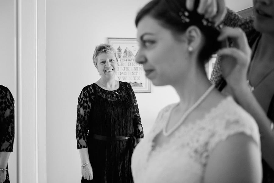 une mère sourie en voyant sa fille se préparer pour son mariage