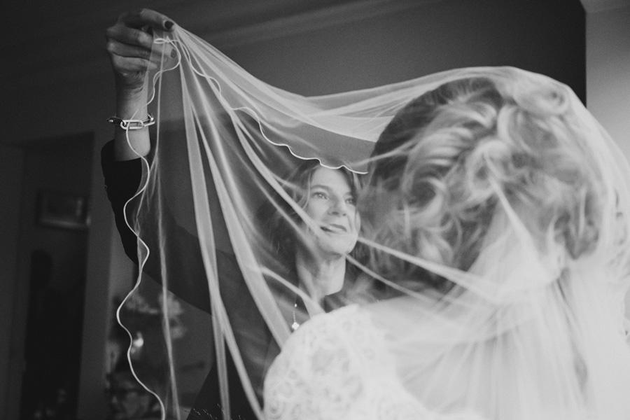 la mère de la mariée l'aide à poser son voile