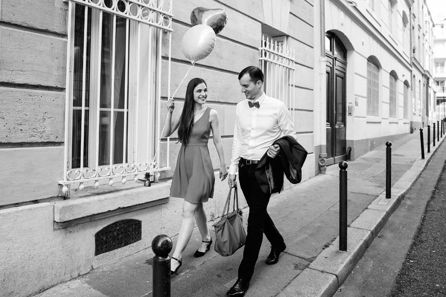 un couple marche dans une rue à Paris avec des ballons