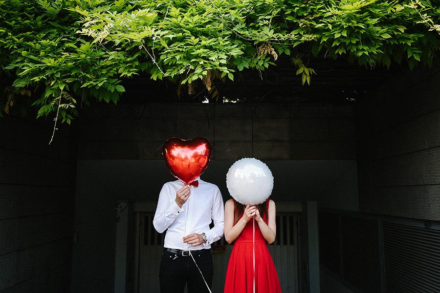 séance engagement Paris, couple avec des visages derrière des ballons