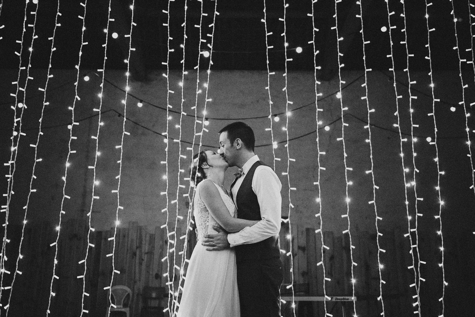 couple mariés devant guirlande lumineuse la nuit