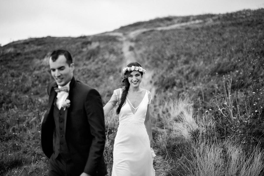 couple marche dans les hautes herbes en se tenant la main
