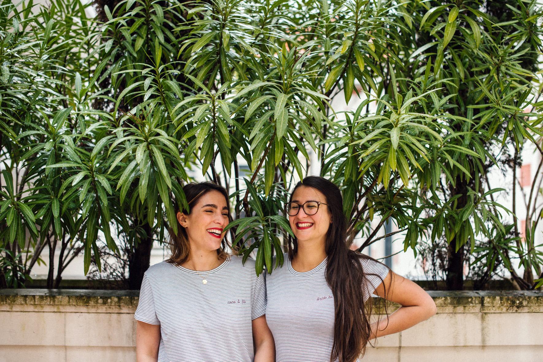 deux femmes rient devant un arbuste
