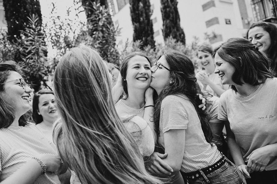 une femme souriante est embrassée par ses amies