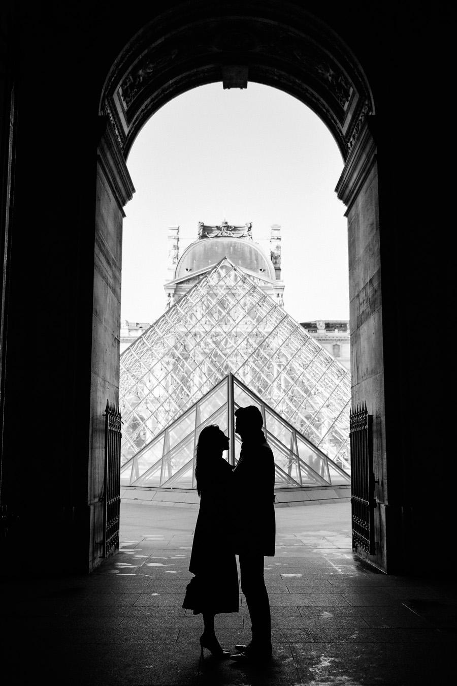 La silhouette d'un couple devant la pyramide du Louvre