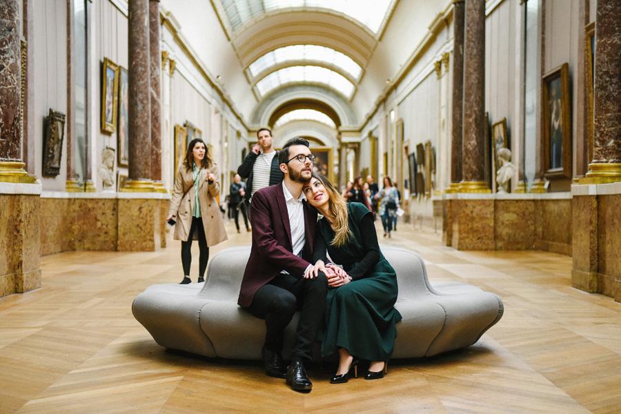 un couple s'enlace dans une galerie du musée du Louvre