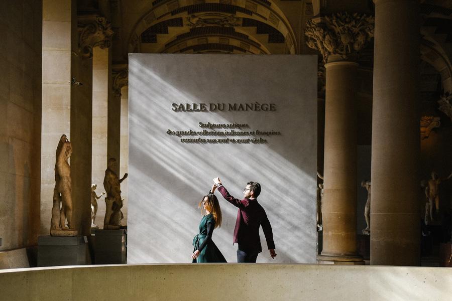 un homme fait danser une femme dans une salle de musée
