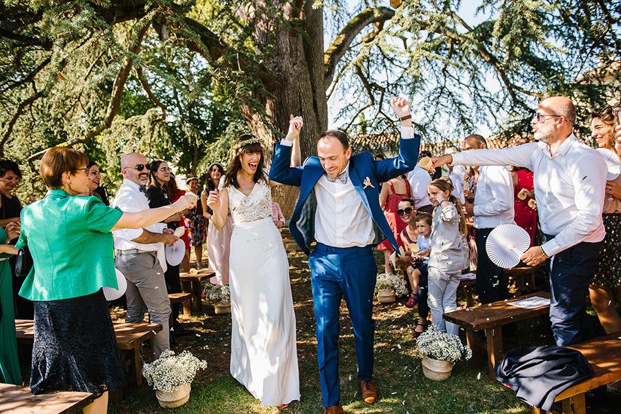 les mariés remontent l'allée des invités après la cérémonie laïque