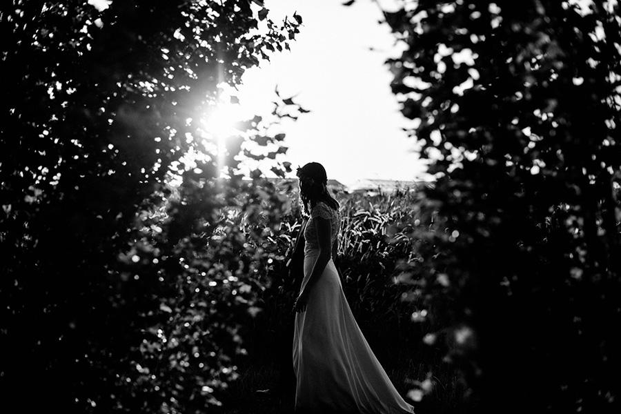 la mariée marche dans un champ au coucher du soleil
