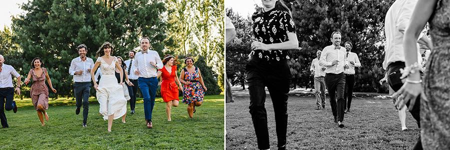 les mariés et leurs amies courent dans un jardin vers le photographe