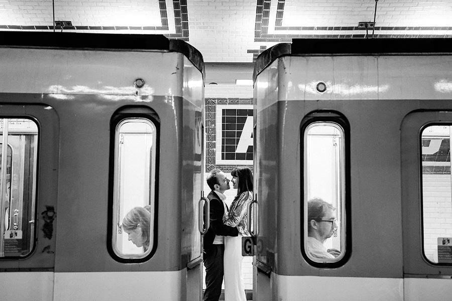 un couple s'enlace entre deux rames de métro