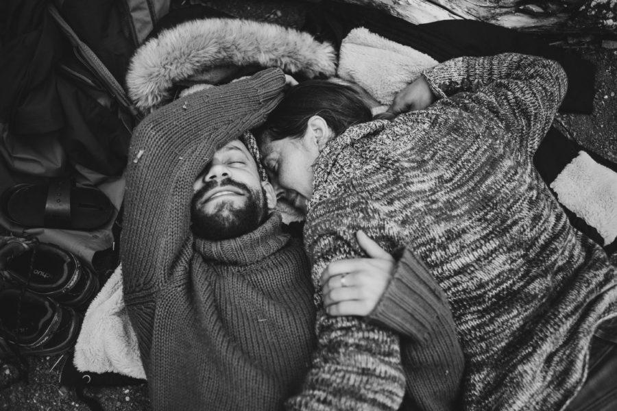 un couple enlacé se repose à même le sol