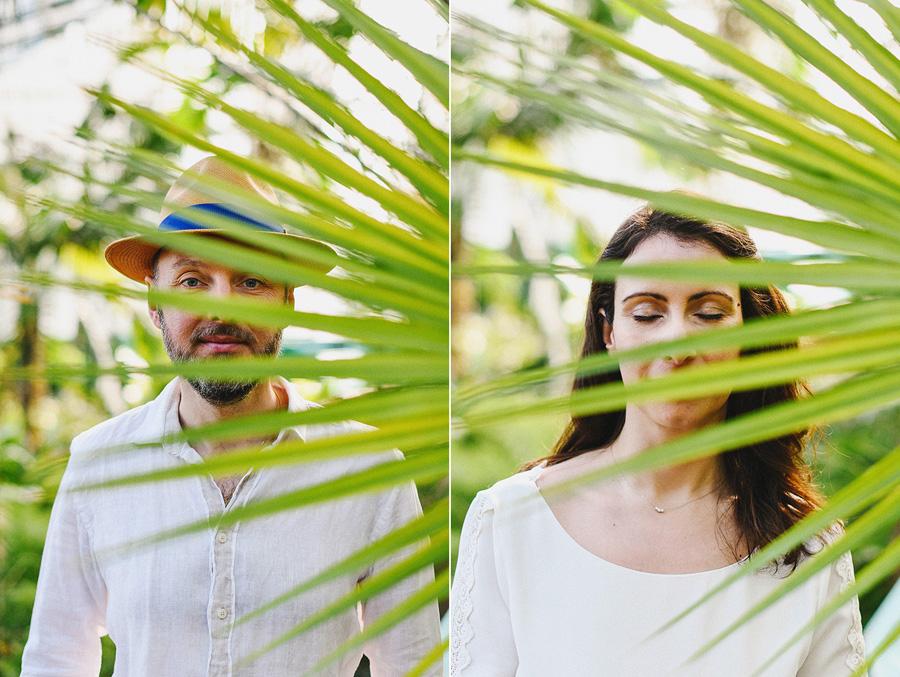 Un homme et une femme sont cachés derrière des feuilles de palmier