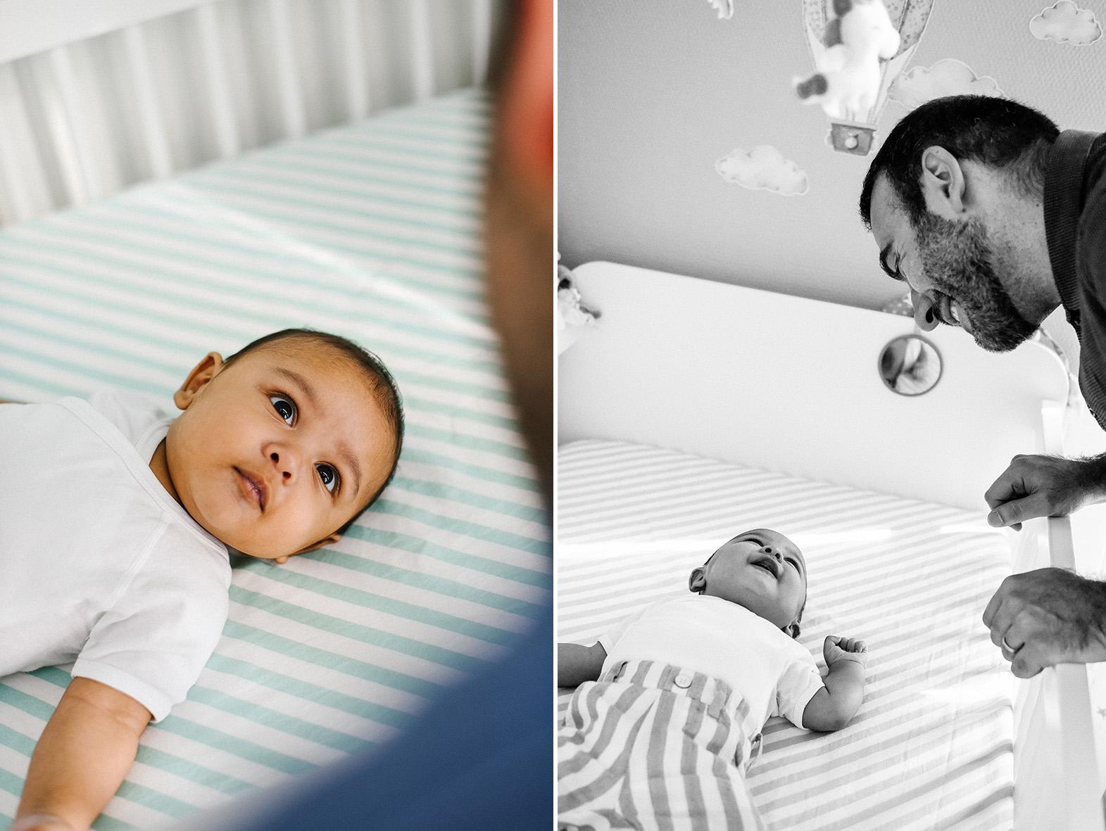 un bébé est allongé dans son lit et regarde son papa