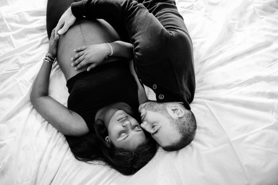 une femme enceinte est allongée sur un lit avec son mari