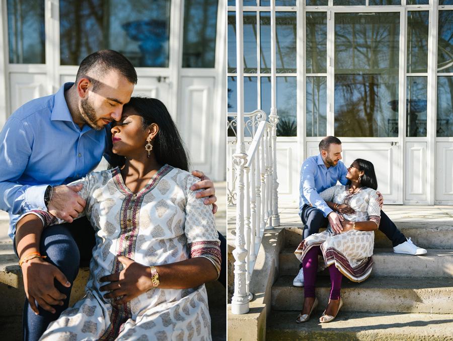 un couple de futurs parents est assis sur des escaliers dans un parc