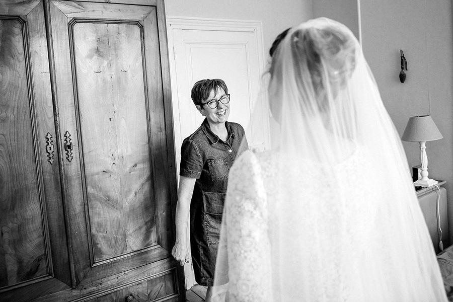 une maman regarde sa fille habillée en robe de mariée