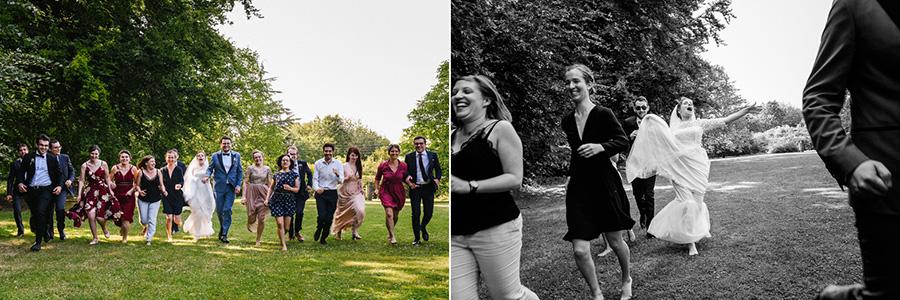 les mariés et leurs amis courent vers le photographe pendant une photo de groupe