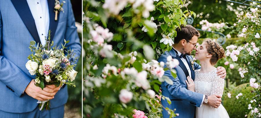 les mariés posent dans une roseraie pendant la séance photo de couple