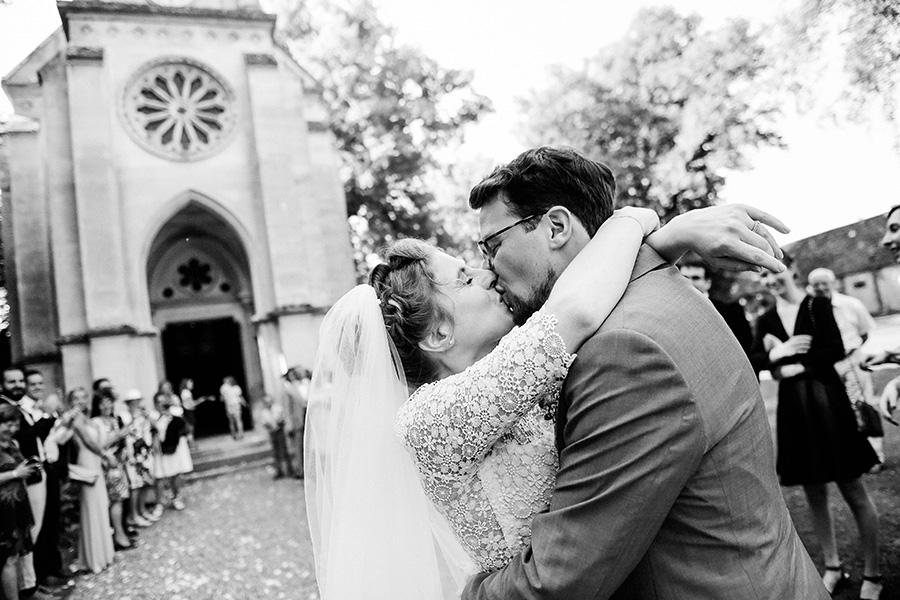 les mariés s'embrassent après la cérémonie religieuse