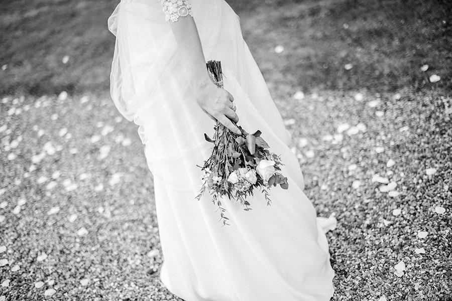 la mariée tient son bouquet de fleurs dans la main
