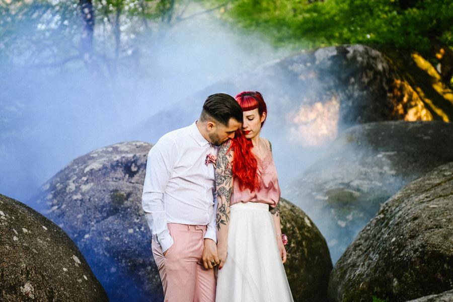 Un couple pose dans des rochers devant de la fumée violette
