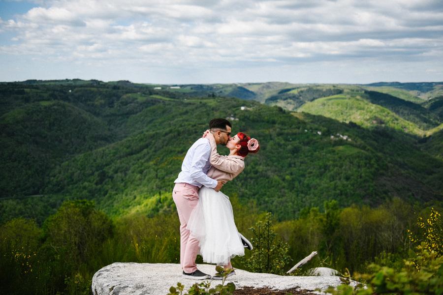 un couple s'embrasse sur un rocher en pleine nature pendant leur elopement