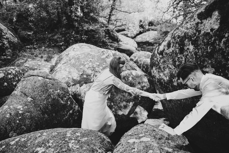 Un couple s'entraide pour marcher au milieu des rochers.