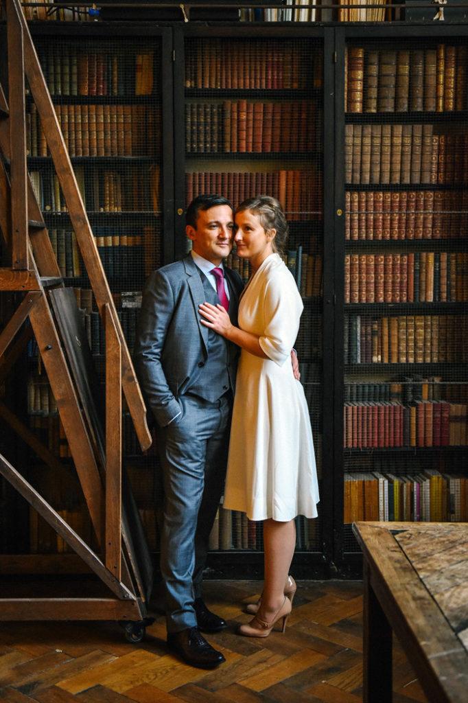 Un couple de jeunes mariés pose devant une bibliothèque