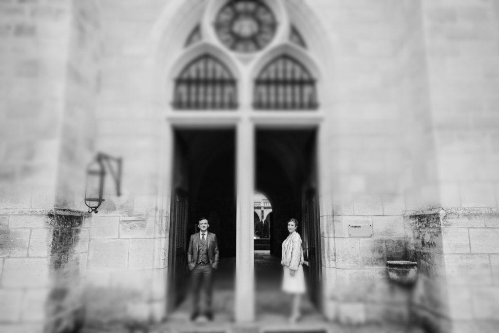 Le couple de mariés se tient devant les murs de l'abbaye