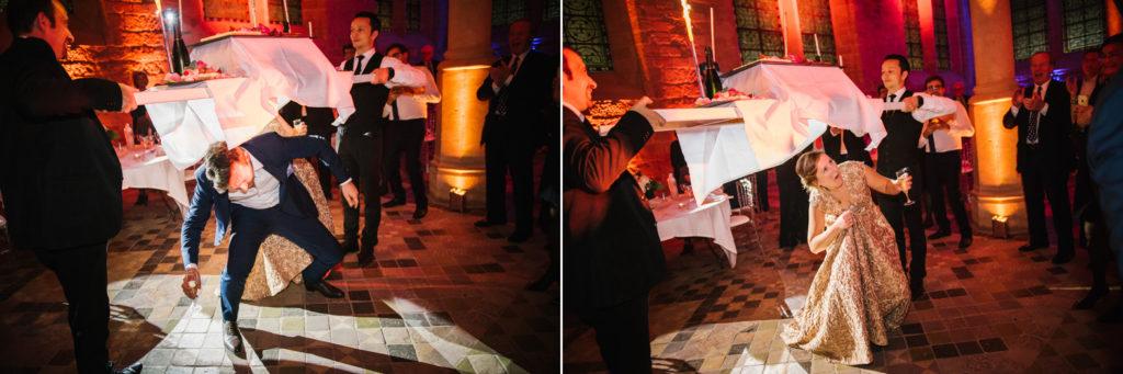 Les mariés se baissent pour passer sous la table du gâteau