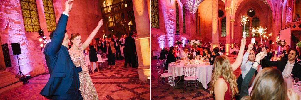 Les invités accueillent les mariés dans la salle avec des scintillants