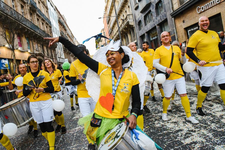 Une troupe de samba batucada défile dans la rue