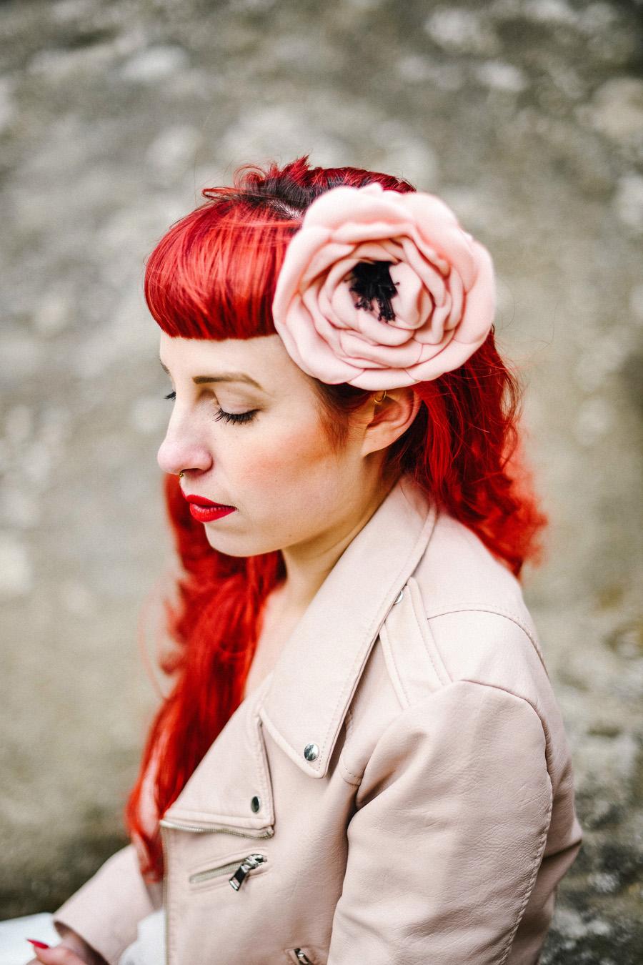 une mariée aux cheveux rouges porte une fleur en tissu rose dans les cheveux