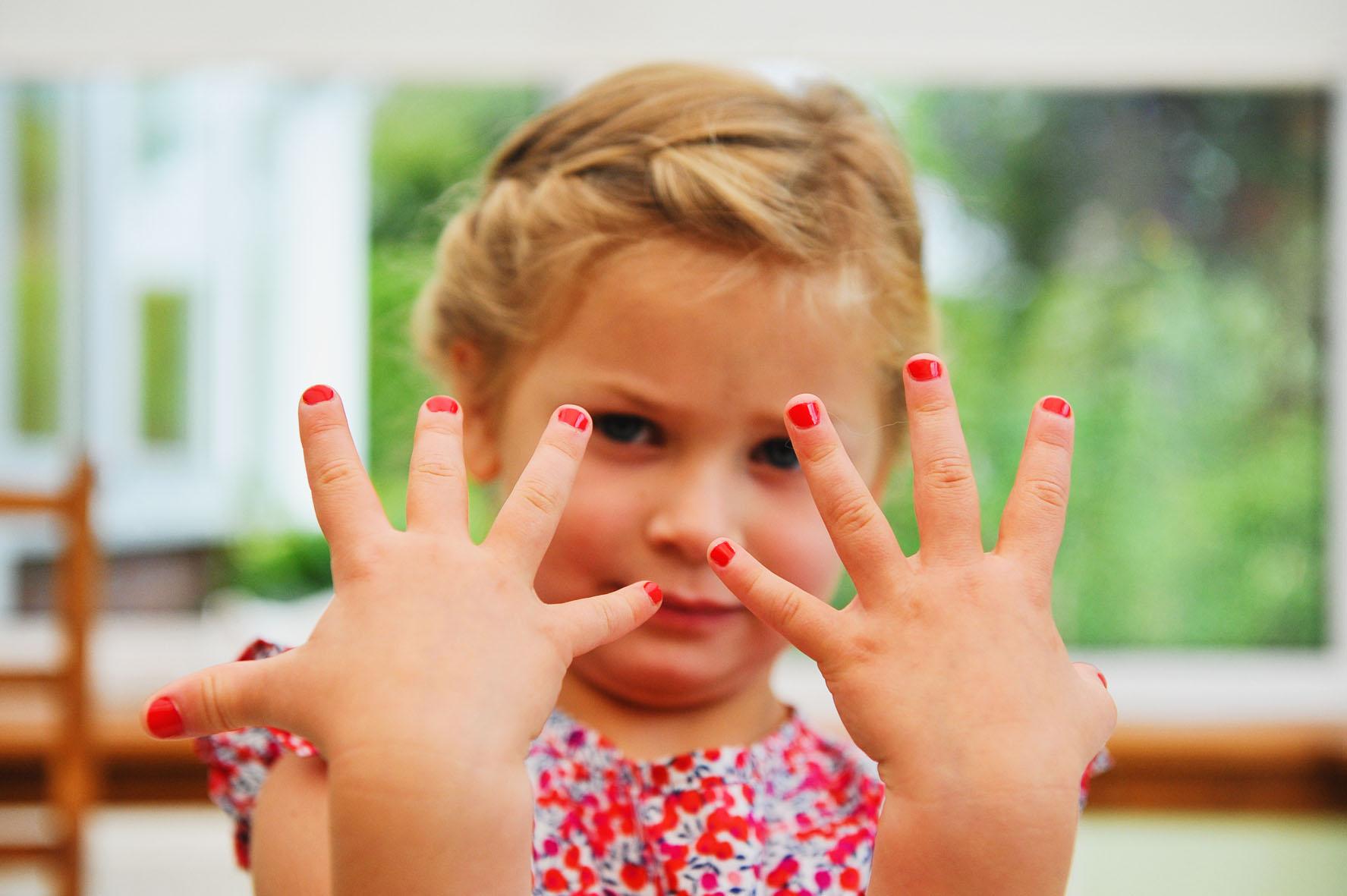 une demoiselle d'honneur montre son vernis à ongles rouge
