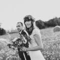 les mariés marchent dans un champ pendant leur séance photo