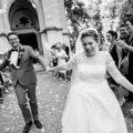 les mariés sortent en courant de l'église après la cérémonie religieuse